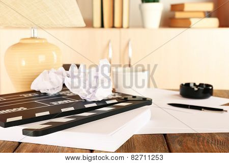Desktop with moving clapper and working mess on light cupboard background