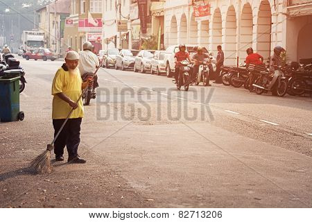 Malaysia, Penang, Georgetown - Circa Jul 2014: Old Man Sweeping The Streets With A Coarse, Handmade