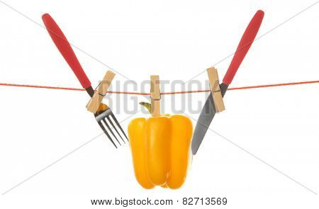 Fork, knife and bell pepper hanging from clothesline isolated on white background