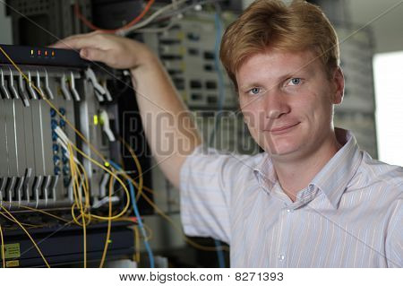 Telecom Engineer Poses On Multiplexer Background