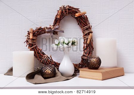 Romantic still life with wicker heart and flowers on mantelpiece and white wall background