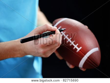 American football star signing autograph on ball on black background