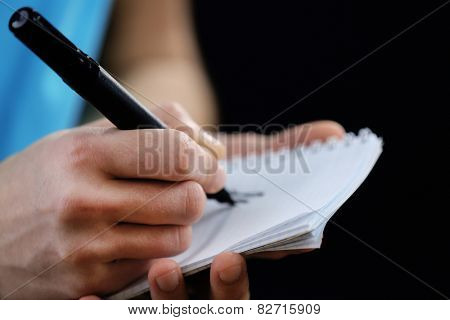 Sportsman signing autograph on small notebook on black background