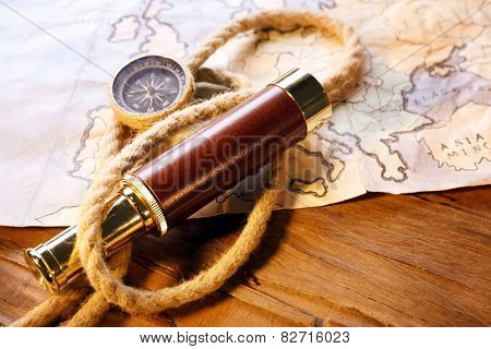 Marine still life spyglass, compass, rope and world map on wooden background