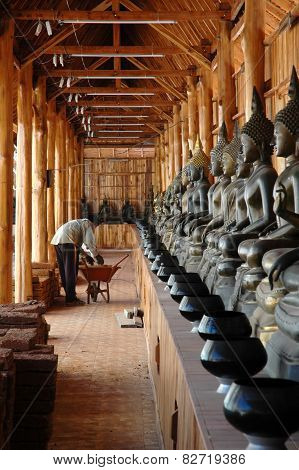 Construction Worker with Row of Buddha Images