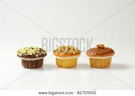 three chocolate muffins on white background