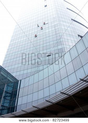 Window Cleaners Climbing Glass Building