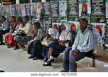 Black People Sit On Bench On Background Of Posters.