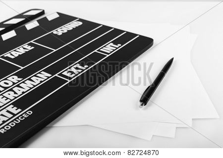 Movie clapper with sheets of paper and pen on white background