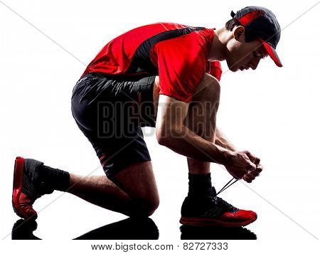 one young man runner jogger lacing shoes in silhouette isolated on white background