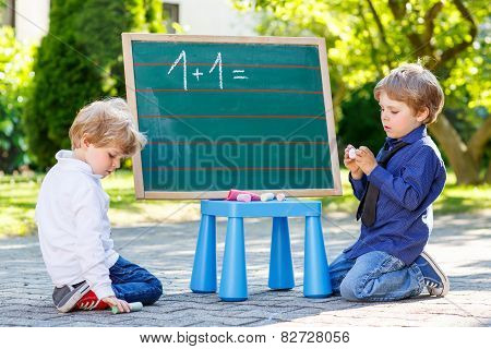 Two Siblinig Boys At Blackboard Practicing Mathematics
