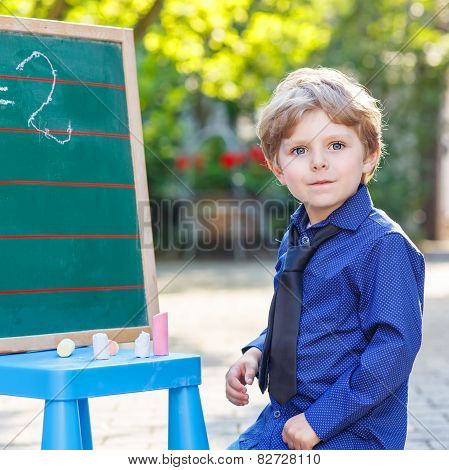 Little Boy At Blackboard Learning To Write