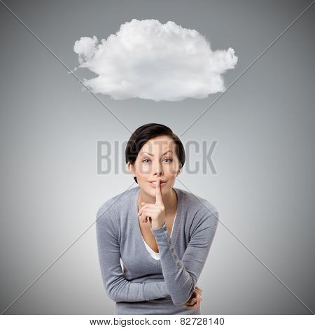 Pretty woman shows silence gesture touching her lips, isolated on grey background with cloud