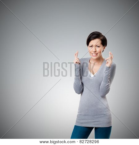 Worrid woman shows crossed fingers, isolated on grey