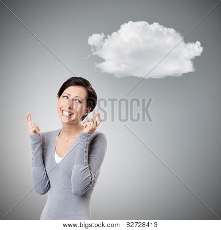 Young woman crosses fingers, isolated on grey background with cloud
