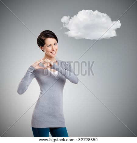 Making a heart hand gesture, isolated on grey  background