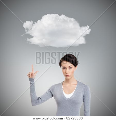 Young woman shows forefinger, attention sign, isolated on grey background with cloud