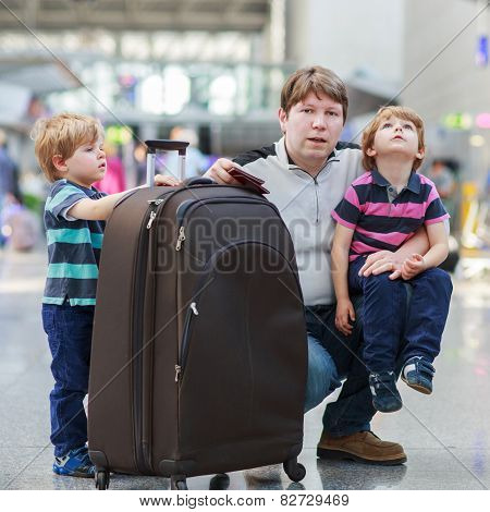 Father And Two Little Sibling Boys At The Airport