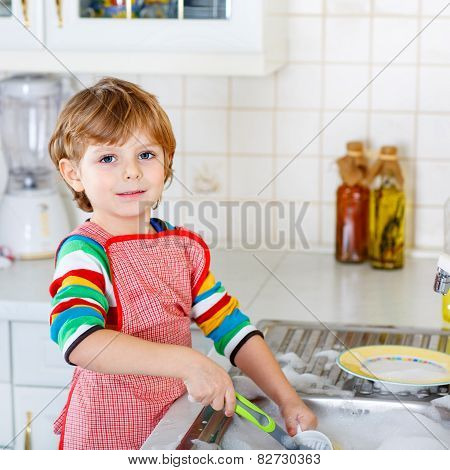 Funny Kid Boy Helping And Washing Dishes At Home