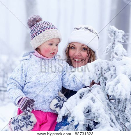 Portrait Of A Little Girl And Mother In Winter Hat In Snow Forest At Snowflakes Background