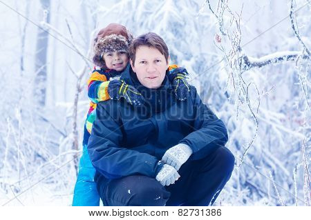 Portrait Of A Little Kid Boy And His Young Father In In Snow Forest