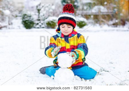 Funny Preschool Boy In Colorful Clothes Making A Snowman
