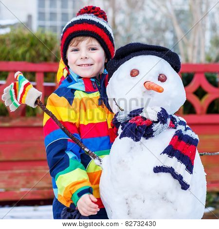 Funny Kid Boy In Colorful Clothes Making A Snowman