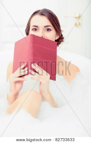 Beautiful young woman in bath with a book