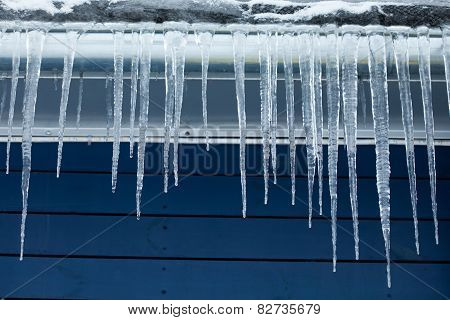 Icicles On The Roof. Winter Concept. Blue Wooden Background.