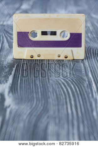 Music Template Postcard. Violet Audio Cassette On The Gray Wooden Background. Vintage, Retro Style.