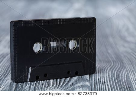 Black Audio Cassette On The Gray Wooden Background. Vintage, Retro Style. Soft Focus.