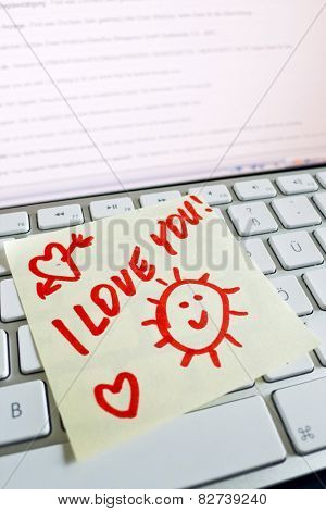a memo is on the keyboard of a computer as a reminder i love you