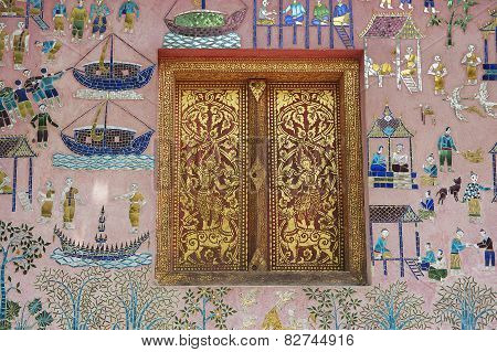 Beautiful mosaic and gold painted window of the pavilion at Xieng Thong temple, Luang Prabang, Laos.