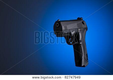 Black handgun sideways isolated on blue background