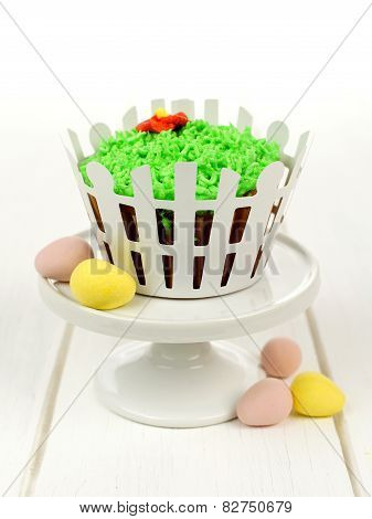 Springtime cupcake decorated with grassWith Grass And White Picket Fence