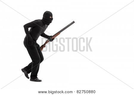 Stealthy criminal with a mask and a rifle walking isolated on white background
