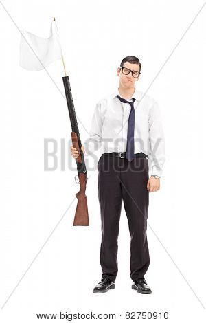 Full length portrait of a sad guy holding a rifle with white flag attached on it isolated on white background
