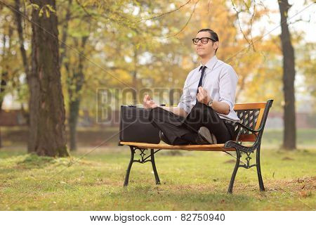 Relaxed businessman meditating seated on a bench in park
