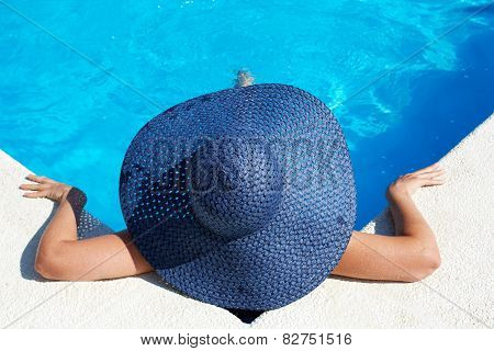 Unrecognizable Woman In Big Hat Relaxing On The Swimming Pool