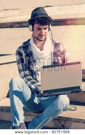 Boy With Laptop In Urban Environment With A Filter Applied Instagram Style And A Flare Effect Added