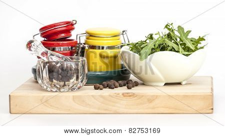 Black pepper in a transparent mortar with a pestle, leaves of arugula and multi-colored containers f