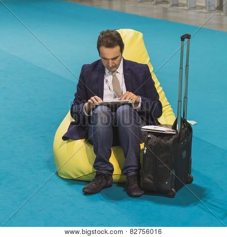 Businessman Working On Tablet At Bit 2015, International Tourism Exchange In Milan, Italy