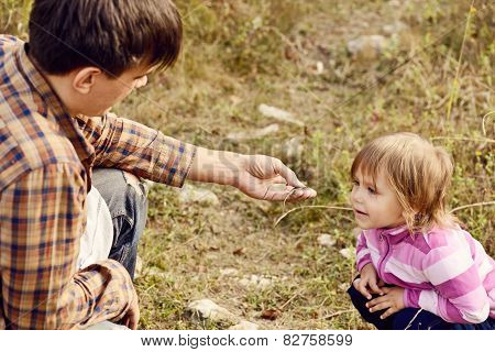 Father Showing Lizard To Daughter