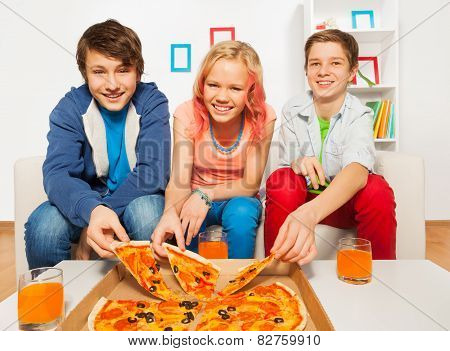 Happy friends holding tasty pizza pieces at home