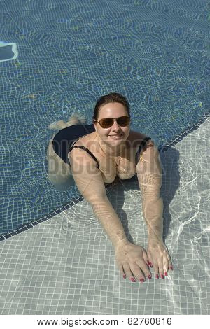 Mid Adult Woman Is Lying Prone In Water Of Pool.