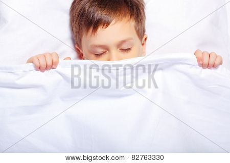 Portrait of a boy sleeping under the blanket