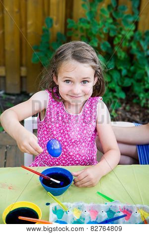 Happy Little Girl Poses With Dyed Blue Easter Egg