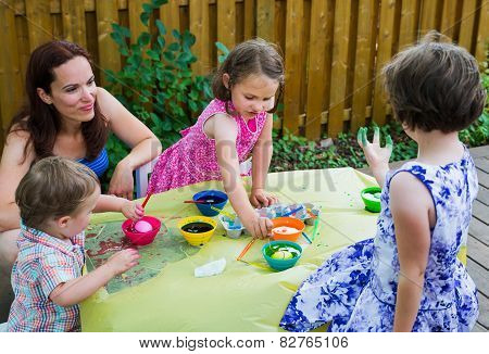 Children Dyeing Easter Eggs Outside