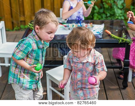 Two Boys Looking At Each Others Colored Easter Eggs