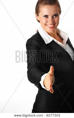 smiling modern business woman stretches out hand for handshake